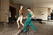 Zwei Frauen laufen durch die Hotel- lounge, Foyer, Treppe, Party-Outfit