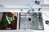 Geschnittene Frühlingszwiebeln auf Holzbrett neben Küchenspüle