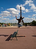 Man jumping on long skateboard in front of Eiffel Tower, Paris