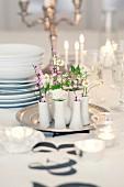 Blumen in kleinen Vasen auf Tablett als festliche Tischdekoration