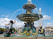 Woman jumping at Fontaine des Mers in Place de la Concorde, Paris, France