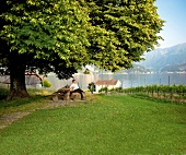 Toni Ottiger sitting on bench near Lake Lucerne and the Alps, Lucerne, Switzerland