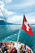 Tourists travelling in boat with national flag, Lucerne, Switzerland