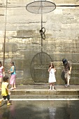 Children playing in water, Paris, France