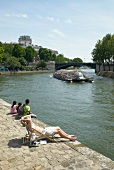 View of Seine river ship and people sitting on promenade, Paris, France