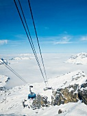 View of Titlis rotating cable car with snow covered mountains, Obwalden, Switzerland