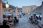 People at restaurant overlooking old harbour in Dubrovnik, Croatia,