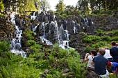 Tourists near waterfall in mountain park, Kassel, Hesse, Germany