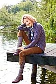 Cheerful blonde woman in purple sweater and brown pants sitting on pier near lake, smiling