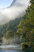 View of Loue river with fog near the village of Lods, Franche-Comte, France