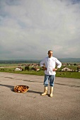 Man standing on road with basket full of sausages beside him, France