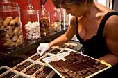 Sylvie Hirsinger arranging chocolates in patisserie, Arbois, Franche-Comte, France