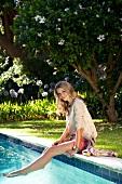 Frau in rosa Shorts sitzt entspannt am Pool, Beine im Wasser