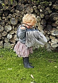 Small girl with curly hair wearing skirt and rubber boots looking into bag