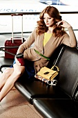 rothaarige Frau wartet am Flughafen auf Abflug, roter Koffer