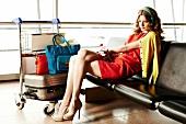 rothaarige Frau wartet am Flughafen auf Abflug, Koffer, Trolley