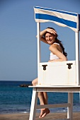 Woman wearing white top sitting in lifeguard tower at beach