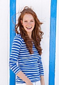 Pretty woman with wavy red hair wearing striped shirt, smiling