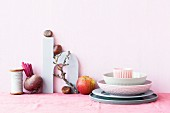An arrangement featuring crockery, anpple, chestnuts, a beetroot and a decorative letter H