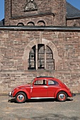 VW beetle red car in front of Parish of Christ the King in Saarbrucken, Germany