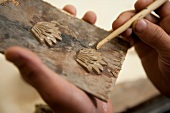 Close-up of human hand making clay art with stick at art school in Thimpu, Bhutan