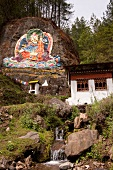 View of rock with Buddha painting and meditation house in Thimpu, Bhutan