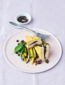 Tofu mit kapernfüllung auf grünen & gelben Zucchinistreifen