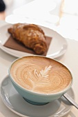 Close-up of cup of coffee with croissant on plate