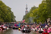 Crowd on boats for gay pride canal parade in Prinsengracht, Amsterdam, Netherlands