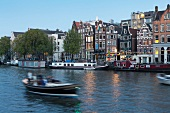 Elevated view of boat, canal and houses in Amstel, Amsterdam, Netherlands, blurred motion