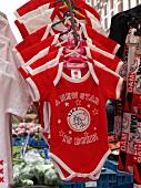 Arrangement of red baby clothes in Albert Cuyp Market, De Pijp, Amsterdam, Netherlands
