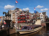 Equestrian monument and ferry in canal in Rokin street, Amsterdam, Netherlands