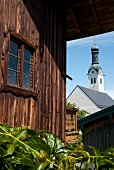 View of Stadtpfarrkirche Sankt Nikolaus through wooden house at Rimsting, Bavaria, Germany