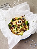 A spaghetti nest in parchment paper with olives, broccoli and dried tomatoes
