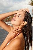 Frau mit langen braunen Haaren und lackierten Fingernägeln unter der Dusche