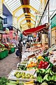 People at market of vegetables in Brixton Village, London, UK