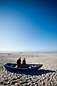 Two people sitting in boat at beach near Kampen, Sylt, Germany