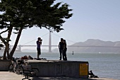 Man photographing couple in front of Golden Gate Bridge, San Francisco, California, USA