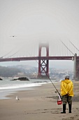 Man on beach fishing in front of Golden Gate Bridge covered with fog, San Francisco, USA