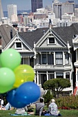People at meadow with balloons in front of houses, San Francisco, California, USA