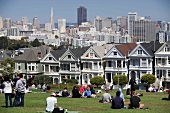 People at meadow in front of postcard row in San Francisco, California, USA