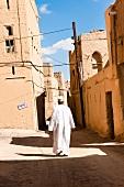 Man wearing dishdasha walking on alley of town with mud houses on side in Al Hamra, Oman