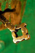 Close-up of ornate gold metal key in Al Hamra, Oman
