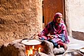 Woman baking traditional bread in Al Hamra, Oman