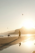 People fishing on Maghsail Bay Beach at sunrise in Salalah, Dhofar, Oman