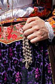 Close-up of woman holding rosary at Cagliari's Sant 'Efisio, Sardinia, Italy