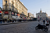 View of Generali building and street with people in Milan, Italy
