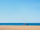 Person on Mediterranean sandy beach in Sardinia, Italy