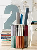 Gestreifter Papierkorb mit Papierrollen vor Bücherstapel und Deko-Zahl
