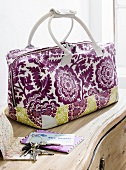 Close-up of flowered Weekender bag with keys and envelopes on table